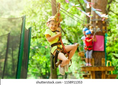 Brave young girl in helmet climbs on tree tops in amusement rope park on summer holidays, children camp