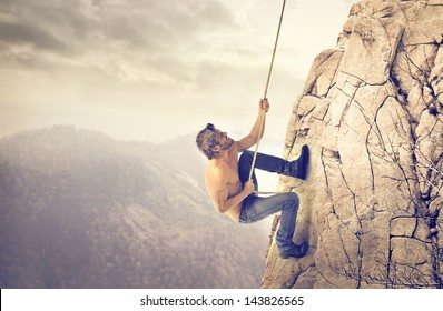 brave young man climbs a mountain