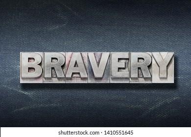 bravery word made from metallic letterpress on dark jeans background