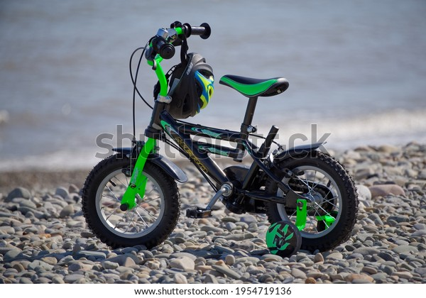 BRAY, CO. WICKLOW, IRELAND - APRIL 3, 2021: Bike for kids with protective helmet hanged on the handlebars and mounted training wheels parked on pebble beach on sunny day.