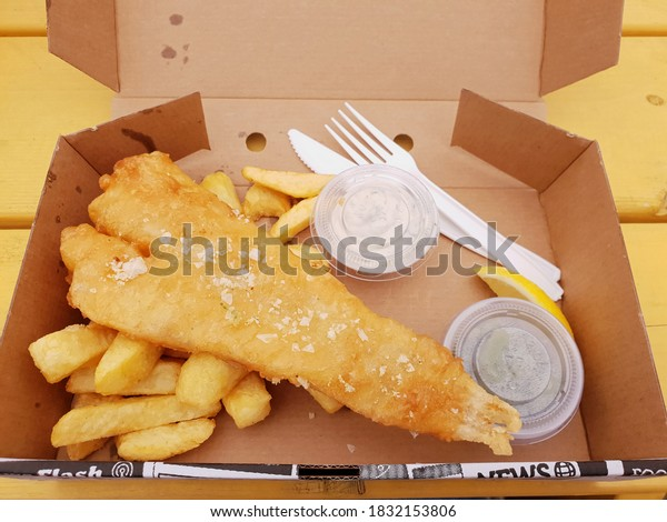 """BRAY, CO. WICKLOW, IRELAND - AUGUST 09, 2020: Close up view of """"Fish and Chips"""" meal. Takeaway food in cardboard box, with white plastic cutlery on yellow wooden table. Top view."""