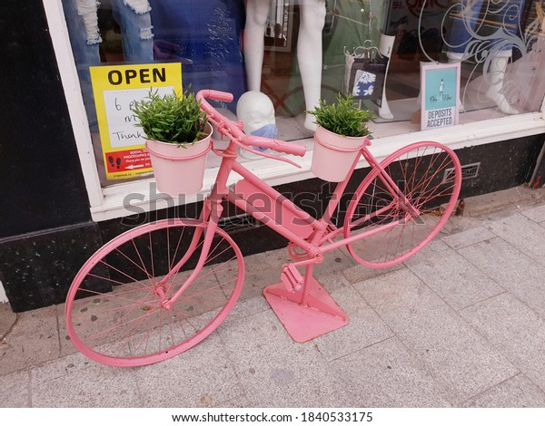 BRAY, CO. WICKLOW, IRELAND - AUGUST 29, 2020: A stand with artificial plants made of an old bicycle painted in pink. An exterior decoration of an clothing store in Bray town, Ireland. Usable art.