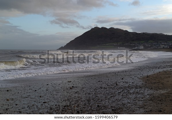 BRAY, CO. WICKLOW, IRELAND - DECEMBER 26, 2019: Seascape with the Irish Sea and the Bray Head mountain. Mist and crashing waves.