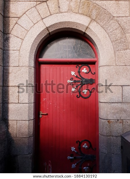 BRAY, CO. WICKLOW, IRELAND - OCTOBER 10, 2020: Side entrance to Catholic church in Bray town. Wooden door painted red, with decorative metal elements. Sunny day.