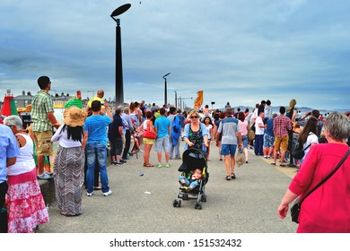 BRAY, IRELAND - July 21: An unidentified woman pushes an unidentified child in a baby buggy through a crowd at The Bray Air Show on July 21, 2013 in Bray, Ireland.