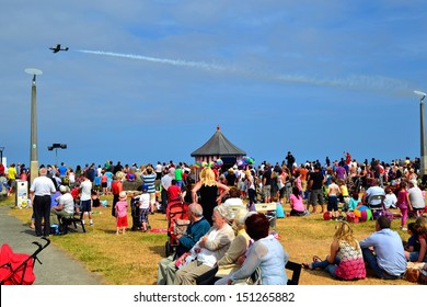 BRAY, IRELAND - JUNE 21: Unidentified onlookers at The Bray Air Show watch a BAC 167 Strikemaster jet flypast on July 21, 2013 in Bray, County Wicklow, Ireland.