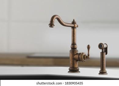 Brazende alte Facette mit kleinem Hebel für die Küche. Brauner Kranich im Nahaufnahme.Moderne Möbel. Kupferwaschbecken als Küchenausstattung. Makrofoto von hoher Qualität.