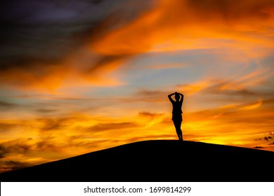 Jalapão, Brazil, 2018 - Woman with arms raised standing over dunes during sunset