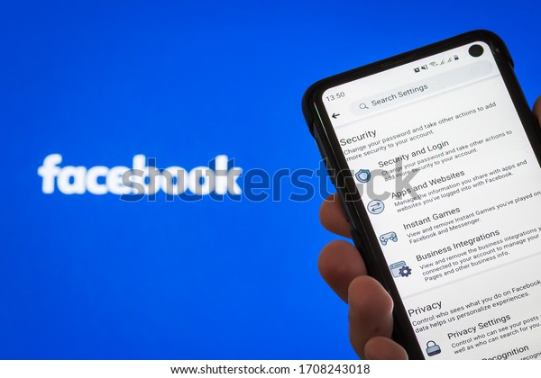 Brazil - April 2020: Hand Holding Mobile Smart Cell Phone Device that Displays Facebook Privacy and Security Settings On Screen With a Facebook Inc. Logo On a Computer Screen On The Background