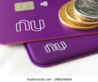 Brazil - August 16, 2019:  Nubank card on a white background and coins. Nubank is a Brazilian company in the segment of financial services and digital bank. largest fintech in Latin America.