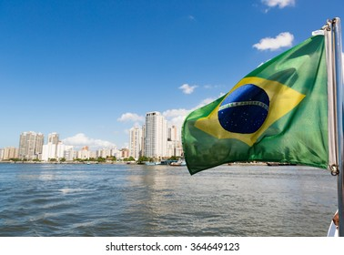 Brazil flag and in the background the city of Santos
