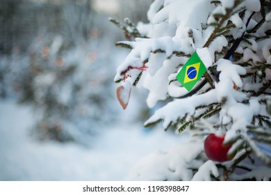 Brazil flag. Christmas background outdoor. Christmas tree covered with snow and decorations and Brazilian flag. New Year / Christmas holiday greeting card.
