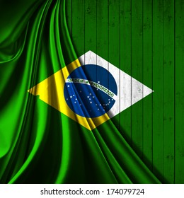 Brazil flag, fabric and green wood background