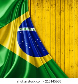 Brazil flag fabric and yellow wood background