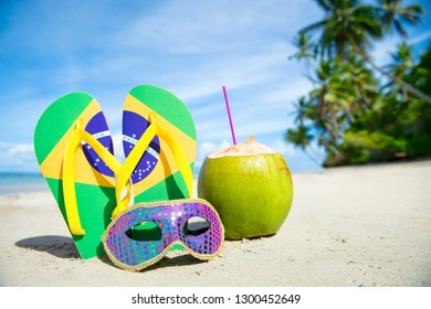Brazil flag flip-flops with brightly sequined carnival mask and fresh drinking coconut resting together in the sand on palm-fringed Brazilian beach. Translation of motto: Order and Progress