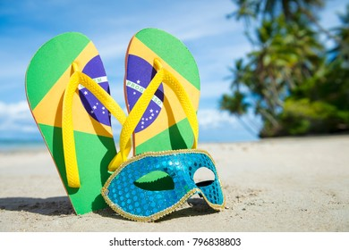 Brazil flag flip-flops and brightly sequined carnival mask resting together in the sand on the shore of a palm-fringed Brazilian beach