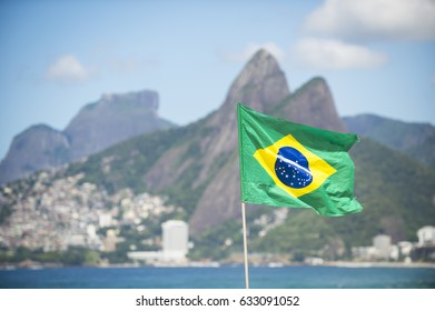Brazil flag flying in the breeze in front of Two Brothers Mountain on Ipanema Beach in Rio de Janeiro
