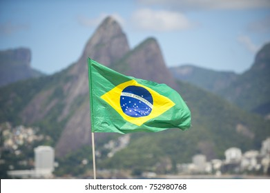 Brazil flag flying in the breeze in front of Two Brothers Mountain on Ipanema Beach in Rio de Janeiro. Translation of motto 'Ordem E Progresso' - Order and Progress.