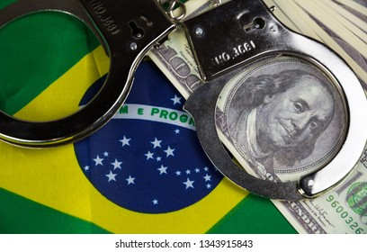 Brazil flag with handcuffs and a bundle of dollars. Currency corruption in the country. Financial crimes