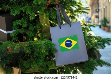 Brazil flag printed on a Christmas shopping bag. Close up of a paper gift bag as a decoration on a Xmas tree on a street. New Year or Christmas shopping, local market sale and deals concept.