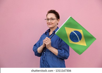 Brazil flag. Woman holding Brazilian flag. Nice portrait of middle aged lady 40 50 years old holding a large flag over pink wall background on the street outdoors.