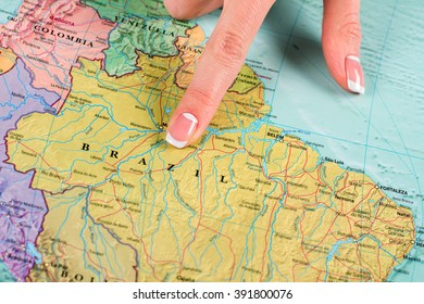 Brazil in geography atlas. Female finger pointing at Brazil. Homeland of great soccer players. Unforgettable place to visit.