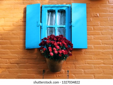 BRAZIL - HOLAMBRA - beautiful and colorful blue window with a flower vase hanging in an orange house