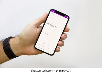 Brazil; July 29, 2019: Man holding smartphone whit a Nubank logo on the screen. Nubank is a Brazilian company in the segment of financial services and digital bank. largest fintech in Latin America.