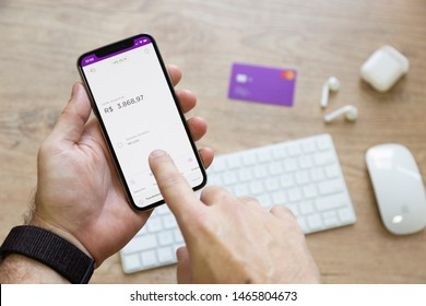 Brazil, July 29, 2019: Man holding smartphone whit a Nubank logo on the screen. Nubank is a Brazilian company in the segment of financial services and digital bank. largest fintech in Latin America.