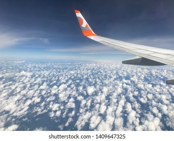 Brasília, Brazil, June 1, 2019: aerial view of the morning landscape, aircraft between many clouds and blue sky in various shades, fog, wing on the left side of the aircraft of GOL