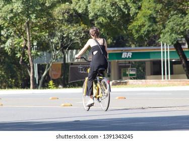 BRASÍLIA, BRAZIL - MAY 5, 2019:  Woman riding an public bike - alternative transportation - at Eixo Rodoviário with buidings and Br PETROBRAS gas station on the background