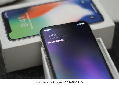"""BRAZIL, MS, CAMPO GRANDE - JUNE 05, 2019: A Box of a new iPhone X being opened with Siri open on the screen saying """"go ahead"""" in Portuguese"""