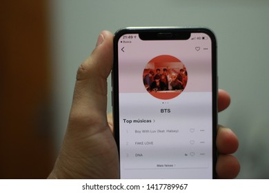 BRAZIL, MS, CAMPO GRANDE - JUNE 06, 2019: A brown man holding an iPhone X with the deezer music app open on profile of BTS band