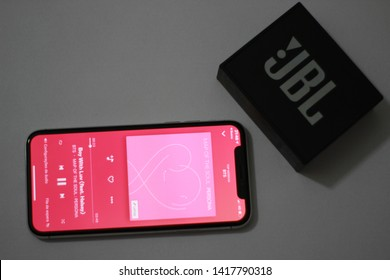BRAZIL, MS, CAMPO GRANDE - JUNE 06, 2019:  An iPhone X with the deezer music app open in the profile of the BTS band playing in a JBL Go sound box