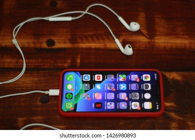 BRAZIL, MS, CAMPO GRANDE - JUNE 17, 2019: Apple iPhone X with red cover on rustic varnished wood table