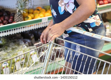 BRAZIL, MS, CAMPO GRANDE - JUNE 26, 2019: lady choosing vegetables to put in supermarket cart.  Supermarket shopping cart of Atacadão