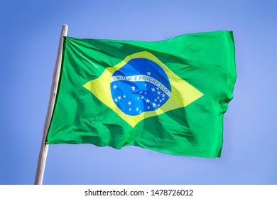 Brazil national flag textile cloth waving on top, blue sky brazil, patriotism concept.