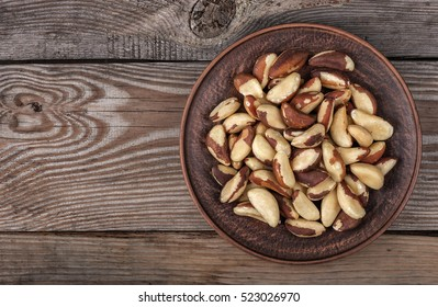 Brazil nuts in a plate on the old wooden background close up top view