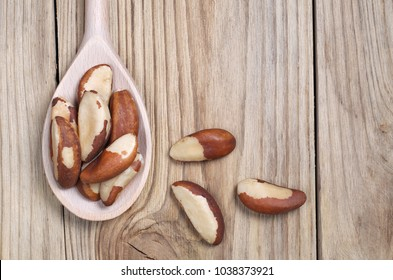 Brazil nuts in wooden spoon on the wooden background, top view