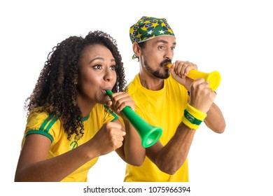 Brazil supporters. Brazilian couple fans celebrating on soccer / football match on white background. Brazil colors. Person is blowing a horn.