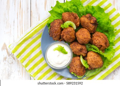 Brazilian acaraje or Nigerian akara snack with black pease or beans; served with green salad and sour cream. Traditional cuisine.