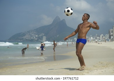 Brazilian altinho player young athletic carioca man juggling football soccer ball on the beach in blue sunga bathing suit Rio de Janeiro Brazil