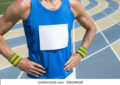 Brazilian athlete in Brazil colored wristbands with blank race bib standing with hands on hips in front of the running track