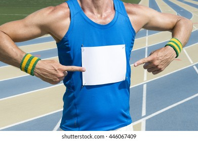 Brazilian athlete in Brazil colored wristbands pointing at blank race bib standing in front of the running track
