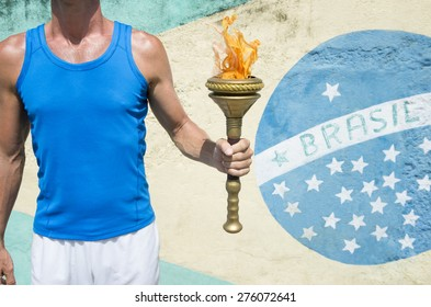 Brazilian athlete holding Olympic sport torch standing in front of a Brasil flag mural Rio de Janeiro Brazil