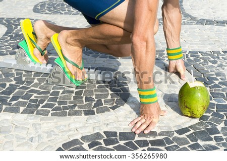 3cb36cc7570414 Brazilian athlete wearing flip flops crouching at the start position in running  blocks with a coconut