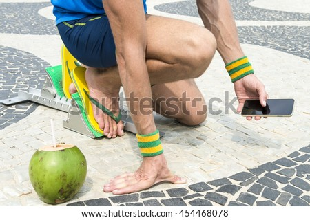 a9a798e294040a Brazilian athlete wearing flip flops crouching at the start position in running  blocks with a coco