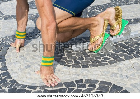 61a1bf7a5f9281 Brazilian athlete wearing flip flops crouching at the start position in running  blocks on the tiles