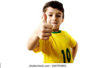 Brazilian boy, soccer player and fan, celebrates on white background. Thumbs up.