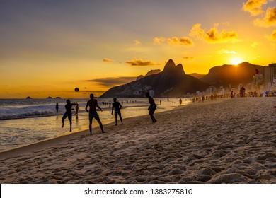 Brazilian boys play football on Ipanema beach at sunset in Rio de Janeiro, Brazil. Ipanema beach is the most famous beach of Rio de Janeiro, Brazil. Sunset cityscape of Rio de Janeiro
